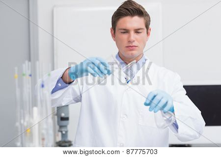 Scientist pouring chemical product in funnel in laboratory