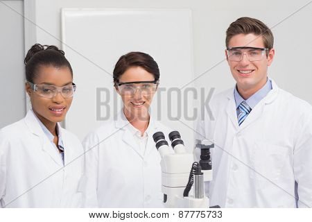 Scientists smiling and looking at camera in laboratory