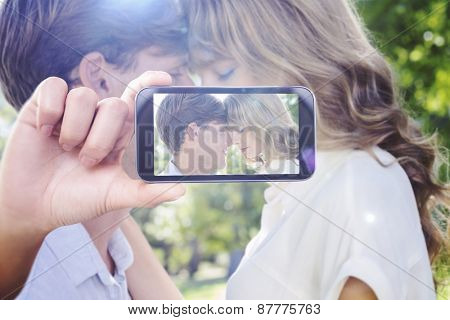 Hand holding smartphone showing against cute couple facing each other in the park