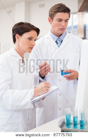 Scientists looking attentively at computer in laboratory