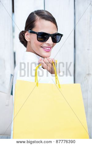 Pretty brunette holding shopping bags in front of wooden grey planks