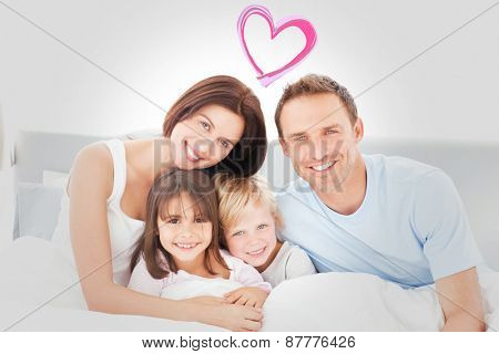 Portrait of a happy family sitting on the bed against heart