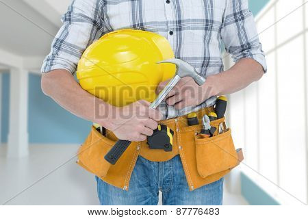 Technician holding hammer and hard hat against modern blue and white room