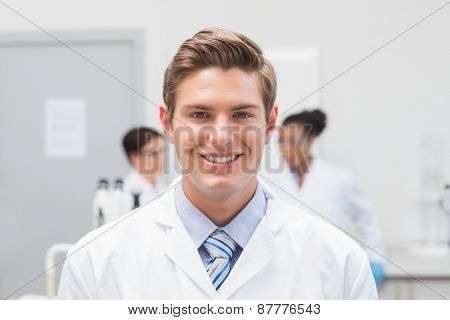 Happy scientist smiling at camera in the laboratory