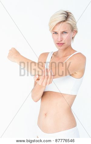 Woman with elbow pain looking at camera on white background