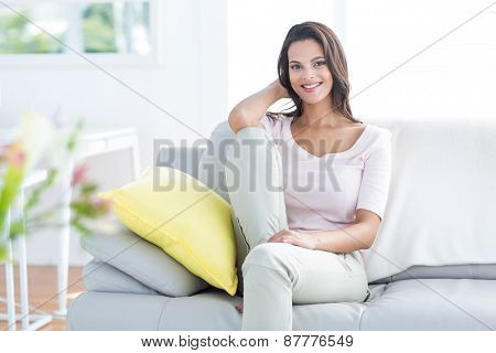 Smiling beautiful brunette relaxing on the couch and looking at camera in the living room