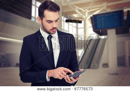 Concentrated businessman in suit using calculator against airport
