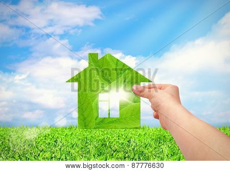 Hand Holding Green House With Field And Blue Sky Background.