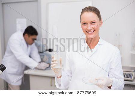 Smiling scientist filling a petri dish in laboratory