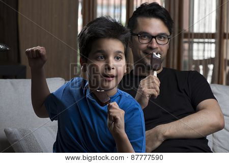 Father and son enjoying chocolate-coated blocks of ice cream on stick.