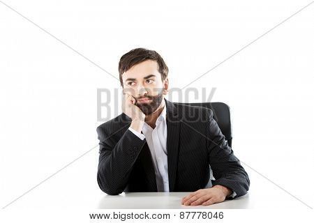 Thoughtful businessman sitting at the desk.