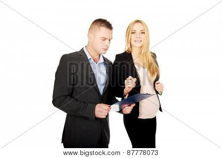 Working pregnant woman signing contract with her partner