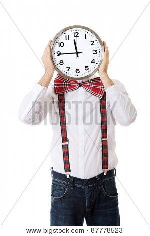 Funny man wearing suspenders hiding behind big clock.