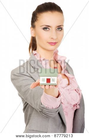Beautiful businesswoman holding a house model.