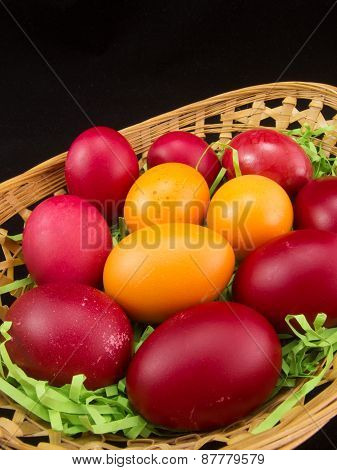 red and yellow easter eggs in basket