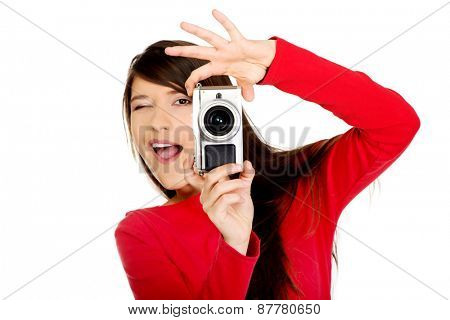 Young woman taking a photo with a camera.