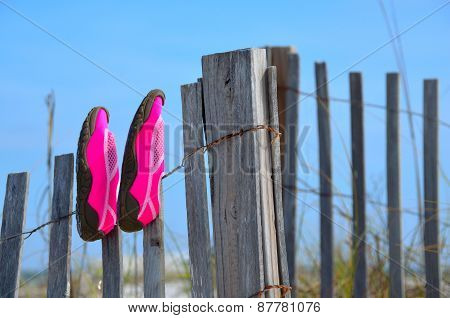 Beach shoes drying on a weathered fence