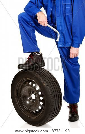 Repairman leg in heavy boots on a tire.