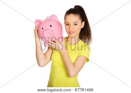 Happy teenage woman holding piggybank.