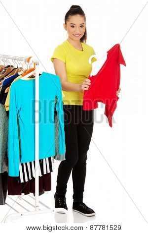 Beautiful young woman with a shirt thinking what to dress.