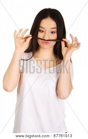 Funny teen woman putting hair like moustache.