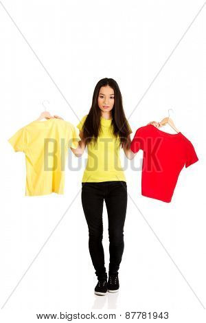 Teen with two shirts thinking what to dress.