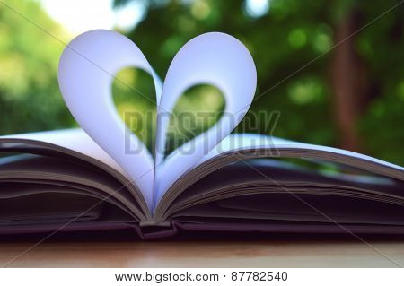 Book pages curved into a shape of heart