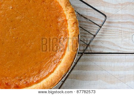 Closeup of a fresh baked pumpkin pie on a cooling rack. Horizontal format with copy space