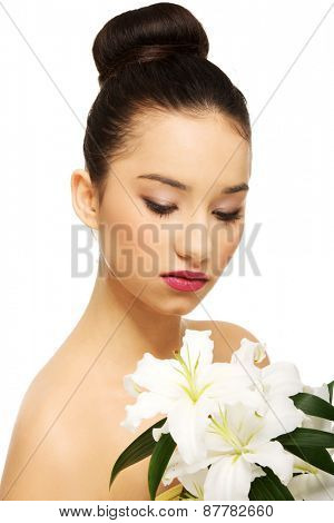 Woman with lily flower and eyes closed.