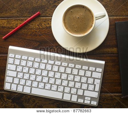 Keyboard, pencil and a Cup of coffee on a dark wooden table, top view.