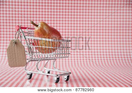 Ripe pear in tiny shopping cart with blank price tag