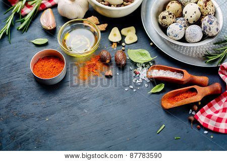 Quail eggs and spices on a dark background