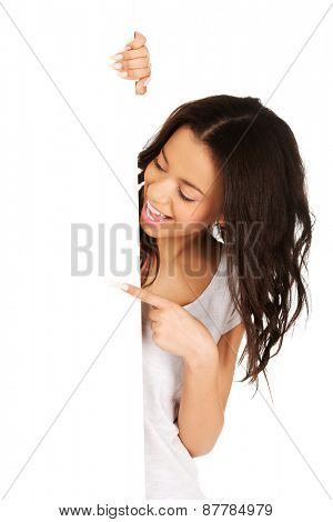 Young african teen pointing on blank board.