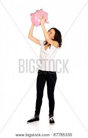 Happy african woman shaking piggybank.
