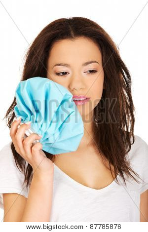 African teen with toothache and ice bag.