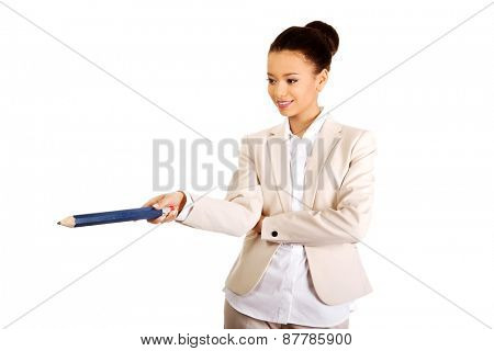 African businesswoman pointing down with big pencil.