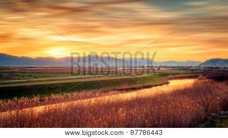 Sunset And Blurred Clouds Illuminate The Fertile Fields
