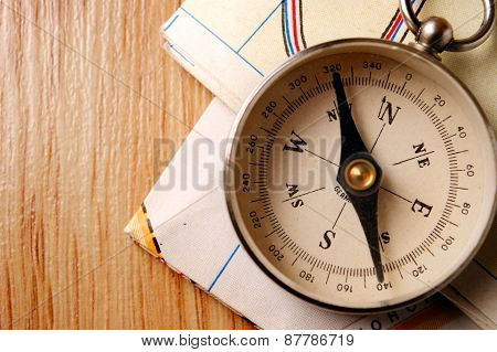 Vintage Compass On Wooden Table With Folded Maps