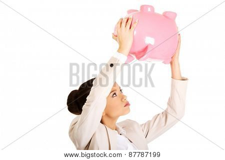 African business woman shaking piggybank.