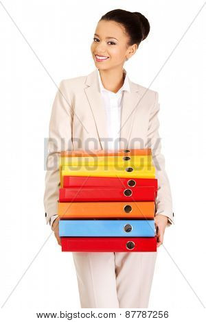 Happy businesswoman holding heavy bidners.