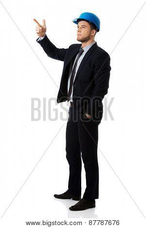 Happy handsome businessman in helmet points his finger up.