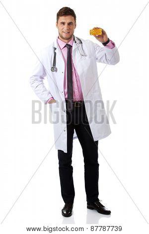 Male doctor or pharmacist holding pills.