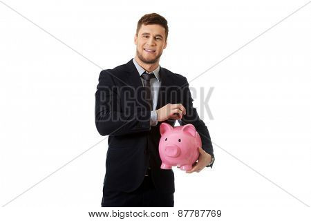 Young businessman holding a piggybank.