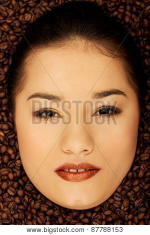 Woman's face in coffee grains.