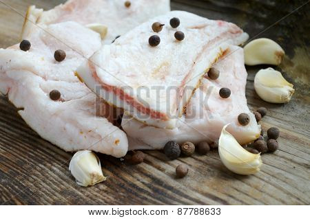 White pork lard called salo with garlic and pepper on wooden kitchen table