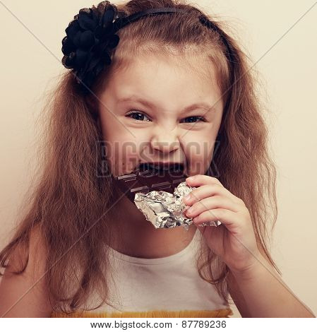 Smiling Kid Girl Biting Dark Chocolate With Craving Fun Eyes. Closeup