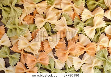 Uncooked butterfly shaped colorful pasta farfalle on wooden table
