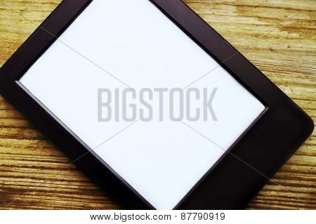 Black ereader with blank screen on wooden table