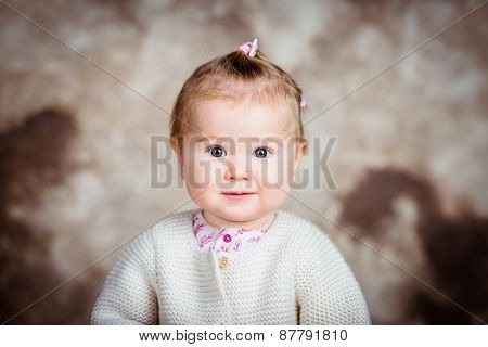 Surprised Blond Little Girl With Big Grey Eyes And Plump Cheeks. Studio Portrait
