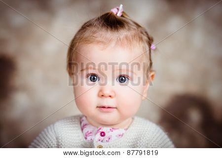 Amazed Little Girl With Big Grey Eyes And Plump Cheeks. Close-up Studio Portrait